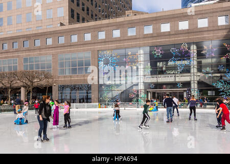 Ice skaters enjoy the Rink at Brookfield Place on a warm winter day in New York City. - Stock Photo