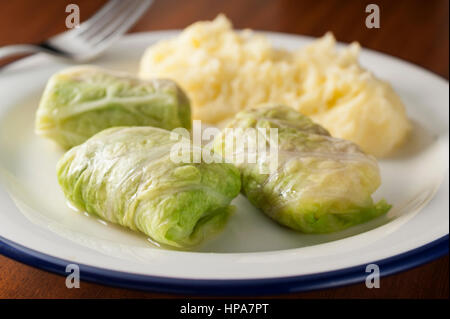 three cabbage rolls stuffed with meat on a white plate with smashed potatoes and a fork - Stock Photo