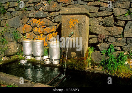 Village water fountain from a well in Auvergne, France with containers to carry water - Stock Photo