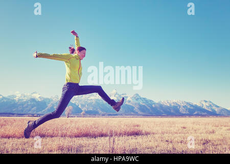 Color toned image of happy young woman jumping on a meadow, Grand Teton mountain range in distance, Wyoming, USA. - Stock Photo
