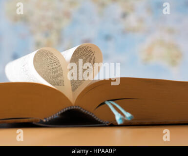 Pages of a book folded in a heart shape, symbolizes love for reading and education - Stock Photo