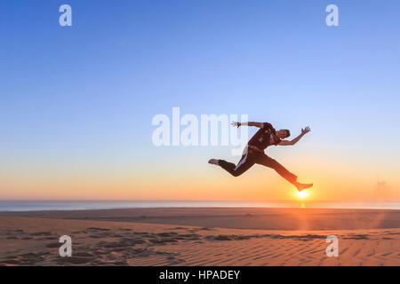 Young man jumping happily in the air, sunset, Namib desert, Langstrand, Swakopmund, Erongo Region, Namibia - Stock Photo
