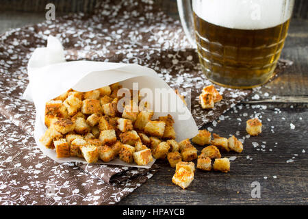 Snack food. Crab crackers, dried white bread and crab sticks and tomato ketchup on the wooden table. - Stock Photo
