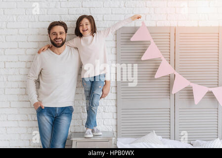 Having fun together. Joyful nice positive father and daughter standing together and laughing while enjoying their - Stock Photo