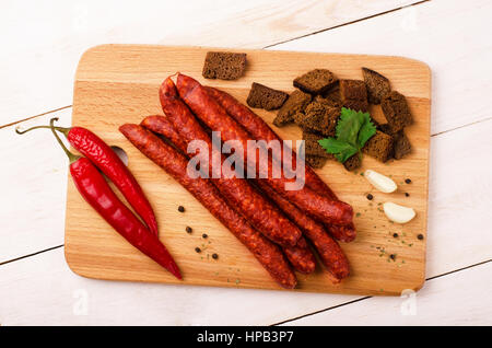 Smoked salami sausage with garlic, croutons and red hot peppers on cutting board - Stock Photo