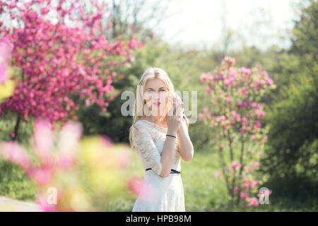 Pretty Blonde Girl Walking in Blooming Spring Sakura Garden - Stock Photo