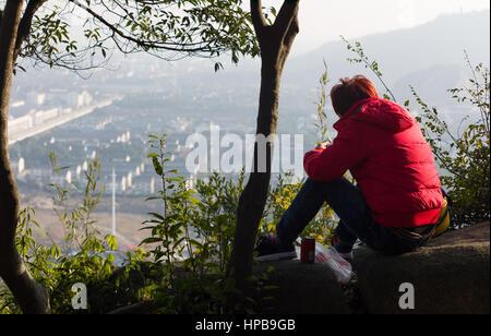 Young man sitting on wall on hillside above urban development, Suzhou, China - Stock Photo