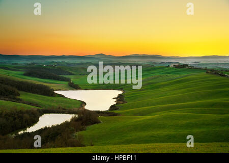 Tuscany, Crete Senesi landscape near Siena, Italy, europe. Small lake, green and yellow fields, blue sky with clouds. - Stock Photo