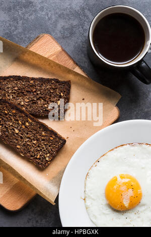 Breakfast with rye bread and fried egg - Stock Photo