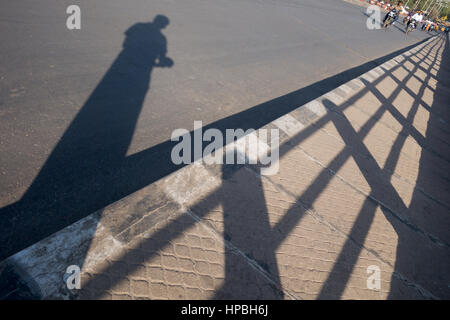 Indian man taking a picture of his own shadow standing on a sidewalk next to railing in Hyderabad,India - Stock Photo