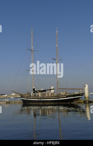 Old wooden black  Ketch docked alongside the jetty at the marina of Lorient, France. - Stock Photo