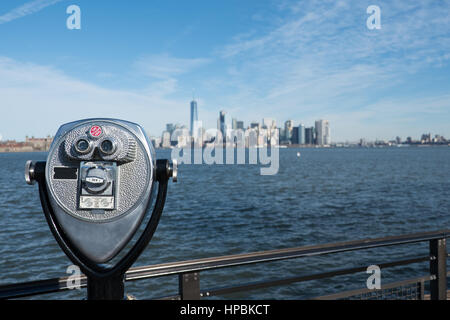 Tower viewer telescope looking at lower Manhattan skyline from Liberty Island. Railing and binoculars on a stand - Stock Photo