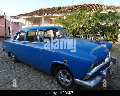Classic american blue car parked on a cobbled  street in Trinidad, Cuba with old colonial buildings on the background - Stock Photo