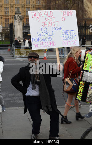 London, UK. 20th February 2017. Trump supporter is dancing at the Parliament Square while holding a placard reading: - Stock Photo