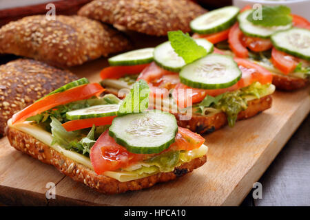 Vegetarian sandwich with pesto on wooden background - Stock Photo