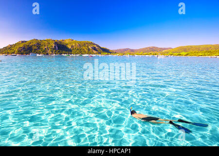 Young attractive man snorkeling in green lagoon in Santa Giulia sandy beach on the south part of Corsica, France, - Stock Photo