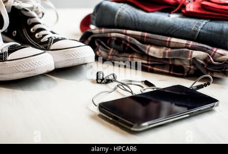 Clothes & accessories: hipster sneakers, denim, plaid shirt, cowboy belt, phone with headphones on wooden background. - Stock Photo