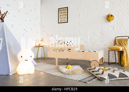 A child's bed in a white bedroom with poured concrete floor a teepee and a white brick wall - Stock Photo