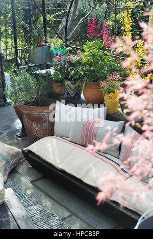A seat on a sunny urban garden patio surrounded by plants in the summer - Stock Photo