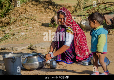 RAJASTHAN, INDIA - NOVEMBER 20, 2016: Rajasthani poor woman cleaning utensils after cooking meal for her family. - Stock Photo