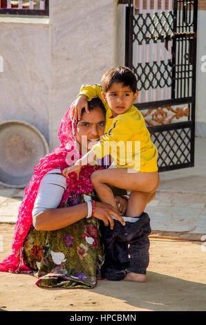 RAJASTHAN, INDIA - NOVEMBER 20, 2016: Young Rajasthani woman helping put on pant to her young son. - Stock Photo