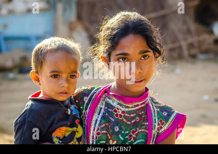 RAJASTHAN, INDIA - NOVEMBER 20, 2016: Unidentified Rajasthani poor young girl holding her brother. - Stock Photo