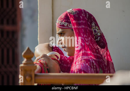RAJASTHAN, INDIA - NOVEMBER 20, 2016: Unidentified Rajasthani woman waiting for someone wearing colorful red sari - Stock Photo