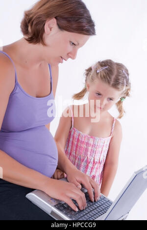 Model released , Schwangere, junge Frau mit Tochter, 4, arbeitet am Laptop - pregnant woman with daughter using - Stock Photo