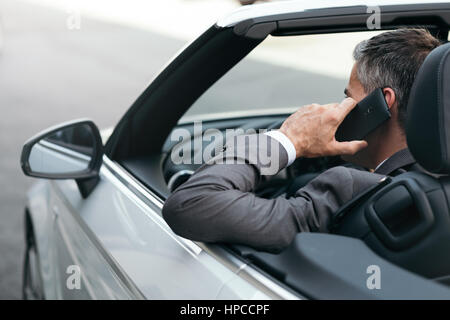 Businessman driving a luxury convertible car and having business phone calls using his smartphone - Stock Photo