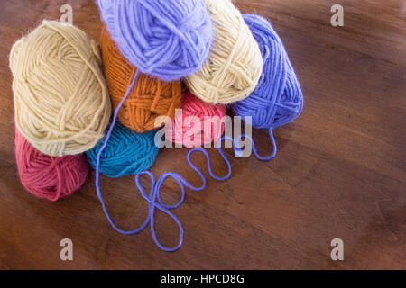 Eight skeins of lavender, cream, gold, turquoise and coral pink wool yarn stacked on a wooden table with the lavender - Stock Photo