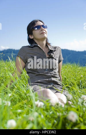 Model released , Junge Frau sitzt in der Sommerwiese - young woman sitting in a meadow - Stock Photo