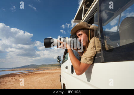 Female safari tourist taking photos from the open window of jeep on game drive in Nakuru - Stock Photo