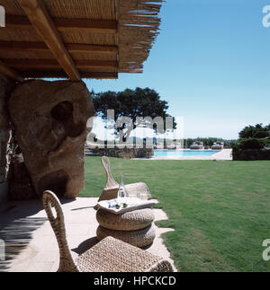 garden park of an italian luxury villa in Port Cervo, Sardinia with two chairs a small table and two glasses of - Stock Photo