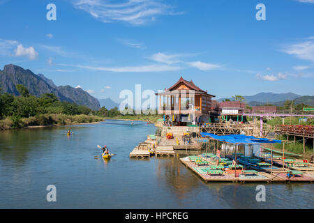 Vang Vieng, Laos - January 19, 2017: Unidentified tourists are rowing kayak boats in Nam Song River in Vang Vieng, - Stock Photo