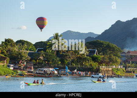 Vang Vieng, Laos - January 19, 2017: Unidentified tourists are riding  speedboats in Vang Vieng village with a hot - Stock Photo