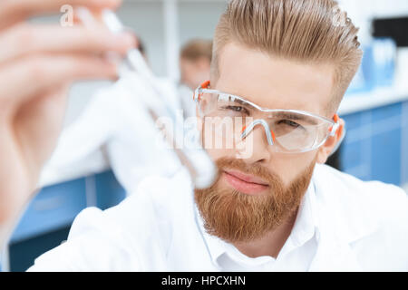 Close-up view of bearded chemist in protective goggles inspecting test tube in lab - Stock Photo