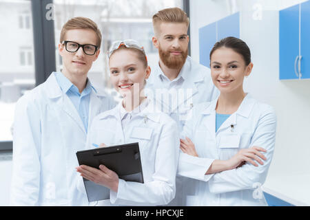 Team of young professional scientists in lab coats smiling at camera - Stock Photo