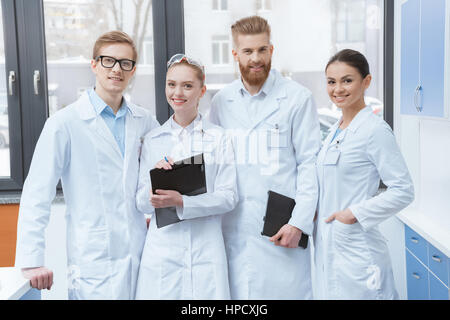 Team of young professional scientists in white coats smiling at camera in laboratory - Stock Photo