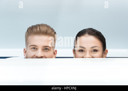 partial view of smiling scientists looking out behind table in lab - Stock Photo