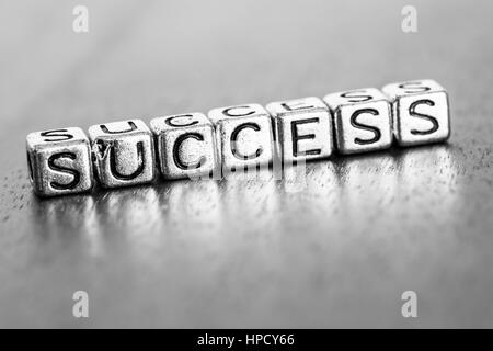 success letters placed on a desk in precious wood - Stock Photo