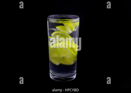 Slices of lime in glass of sparkling water on black background.Popular and tasty summer drink,cold lemonade.Aesthetic - Stock Photo