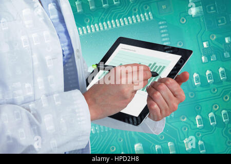 Midsection of female doctor using digital tablet with stylus against green and black electronic circuit - Stock Photo