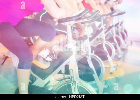 Spin class working out in a row against abstract background - Stock Photo