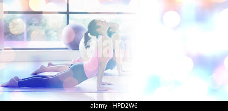 Fit women doing the cobra pose in fitness studio against glowing background - Stock Photo