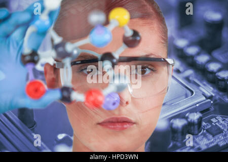 Portrait of female scientist holding molecular model against detail shot of computer chip - Stock Photo