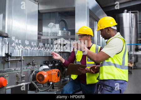 Two factory workers discussing while monitoring drinks production line at factory - Stock Photo