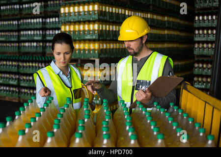 Two factory workers monitoring cold drink bottles at drinks production factory - Stock Photo
