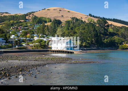 Akaroa, Canterbury, New Zealand. View along the shore of Akaroa Harbour at low tide, wooden boathouse prominent. - Stock Photo