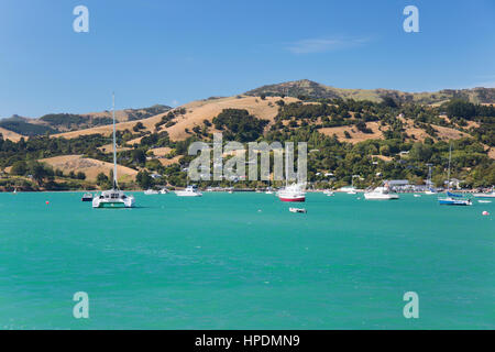 Akaroa, Canterbury, New Zealand. View across the turquoise waters of Akaroa Harbour to the rolling hills of the - Stock Photo