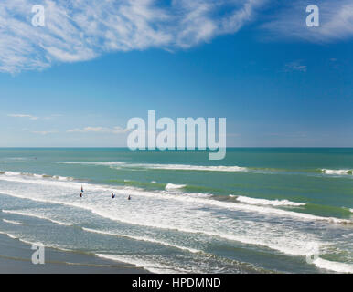 Christchurch, Canterbury, New Zealand. View over the Pacific Ocean off New Brighton Beach, young bodyboarders preparing - Stock Photo